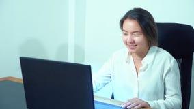 Computer portatile asiatico sveglio di uso della ragazza alla tavola in ufficio video d archivio