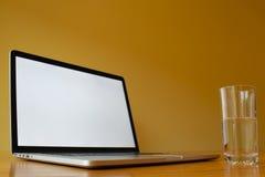 Computer portatile in bianco con bicchiere d'acqua Fotografia Stock Libera da Diritti