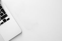 Computer portatile bianco con la tastiera nera sul fondo della tavola Immagini Stock Libere da Diritti