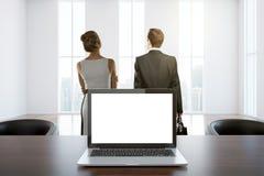 Computer portatile bianco nella sala con la gente Fotografia Stock