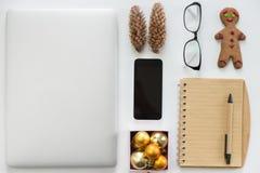 Computer portatile chiuso, telefono cellulare, articoli per ufficio e decorazione di Natale Fotografia Stock Libera da Diritti
