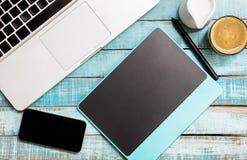 Computer portatile, compressa e pnone piani di disposizione su legno blu Fotografie Stock