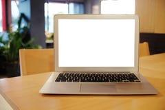 Computer portatile con derisione sullo schermo in bianco sulla tavola di legno davanti allo spazio del caffè del coffeeshop per t fotografia stock