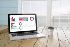 computer portatile con i grafici sullo schermo con il fondo ed il caffè del porto Immagine Stock Libera da Diritti