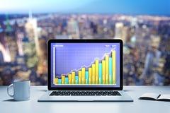 Computer portatile con il grafico commerciale su una tavola nell'ufficio di sera Immagine Stock