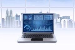 Computer portatile con il grafico finanziario in ufficio Fotografia Stock Libera da Diritti