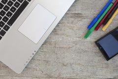 Computer portatile con il telefono cellulare ed alcune penne di colore su una tavola di legno w Fotografia Stock