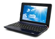 Computer portatile con la carta da parati blu del cielo nuvoloso Fotografia Stock Libera da Diritti