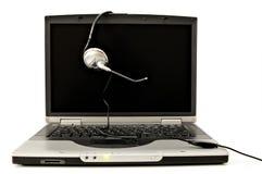 Computer portatile con la cuffia avricolare Fotografie Stock Libere da Diritti