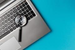 Computer portatile con la lente d'ingrandimento fotografia stock libera da diritti