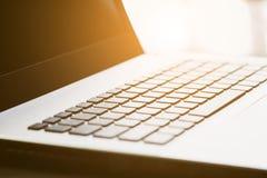 Computer portatile con la luce del chiarore sull'ufficio dello scrittorio Fotografia Stock Libera da Diritti