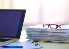 Computer portatile con la pila di cartelle sulla tavola su bianco Immagine Stock Libera da Diritti