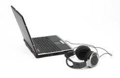 Computer portatile con le cuffie. Fotografia Stock