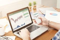 Computer portatile con le statistiche finanziarie su un desktop fotografia stock