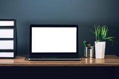 Computer portatile con lo schermo in bianco sul desktop dell'ufficio Immagini Stock