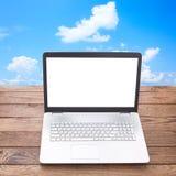 Computer portatile con lo schermo bianco sul posto di lavoro di legno della tavola Immagine Stock Libera da Diritti