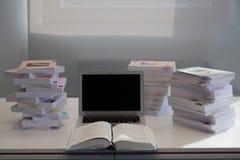 Computer portatile con uno schermo in bianco sullo scrittorio con le pile di b Immagini Stock