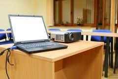 Computer portatile connesso al proiettore sulla tabella Fotografia Stock