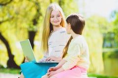 Computer portatile del gioco di bambini Ragazze che si siedono contro gli alberi e lago all'aperto Immagini Stock Libere da Diritti