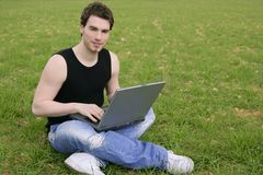 Computer portatile del giovane dell'allievo sul prato Fotografie Stock