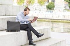 Computer portatile dell'uomo d'affari nella via. immagine stock