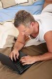 Computer portatile della camera da letto dell'uomo Fotografia Stock Libera da Diritti