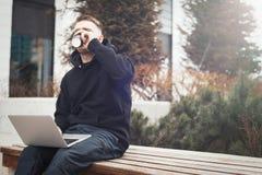 Computer portatile della tenuta del giovane sul caffè bevente del kneesand dalla tazza nera Fotografia Stock