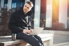 Computer portatile della tenuta del giovane sulle ginocchia La tazza di caffè nero è accanto lui Fotografia Stock