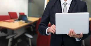 Computer portatile della tenuta dell'uomo d'affari fotografia stock libera da diritti