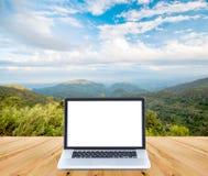 Computer portatile dello schermo in bianco su legno con la montagna ed il cielo blu Fotografia Stock Libera da Diritti