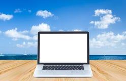 Computer portatile dello schermo in bianco sul pavimento di legno con l'oceano e la s blu Immagini Stock