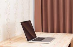 Computer portatile dello schermo in bianco sulla tavola di legno Immagini Stock