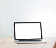 Computer portatile dello schermo in bianco sulla tavola di legno Immagine Stock