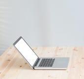 Computer portatile dello schermo in bianco sulla tavola di legno Immagine Stock Libera da Diritti