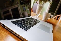 Computer portatile di lusso visto su un tavolo da cucina durante una pausa caffè fotografia stock libera da diritti