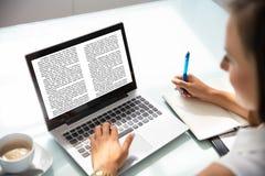 Computer portatile di Reading Information On della donna di affari fotografie stock