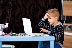 Computer portatile di sguardo del bambino Immagine Stock