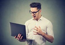 Computer portatile di sorveglianza arrabbiato del giovane nella collera fotografie stock libere da diritti