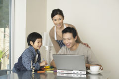 Computer portatile di sorveglianza di uso dell'uomo del figlio e della donna fotografia stock