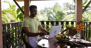 Computer portatile di uso del giovane sulla seduta sorridente felice del terrazzo al tipo ispano della Tabella all'aperto archivi video