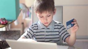Computer portatile di uso del ragazzino e carta di credito svegli archivi video