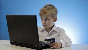 Computer portatile di uso del ragazzino e carta di credito svegli stock footage