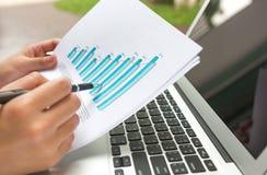 Computer portatile di uso dell'uomo d'affari con il diagramma finanziario Fotografia Stock