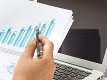 Computer portatile di uso dell'uomo d'affari con il diagramma finanziario Immagini Stock