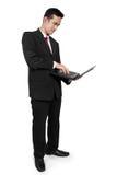 Computer portatile di uso di condizione dell'uomo d'affari immagine stock