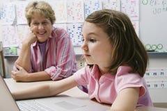 Computer portatile di Watching Schoolgirl Use dell'insegnante Immagini Stock Libere da Diritti