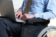 Computer portatile disabile di In Wheelchair Using dell'uomo d'affari fotografie stock