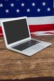 Computer portatile e bandiera americana sulla tavola di legno Immagini Stock