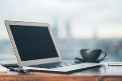 Computer portatile e caffè sulla tavola Fotografia Stock Libera da Diritti