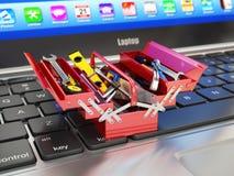 Computer portatile e cassetta portautensili con gli strumenti Appoggio online Immagine Stock